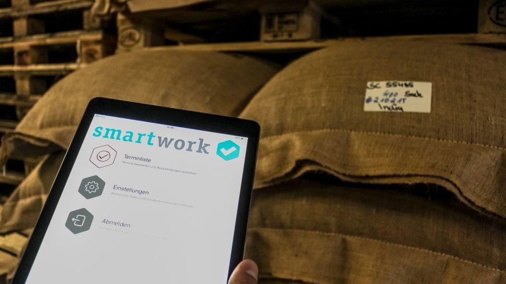 Eine Hand hält ein Tablet mit smartwork mobile. Im Hintergrund sind Säcke und Paletten in einem Lager zu sehen.